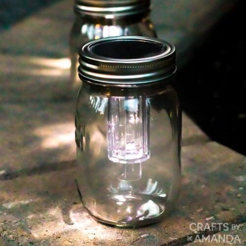 3 mason jar solar lights on a firepit ledge