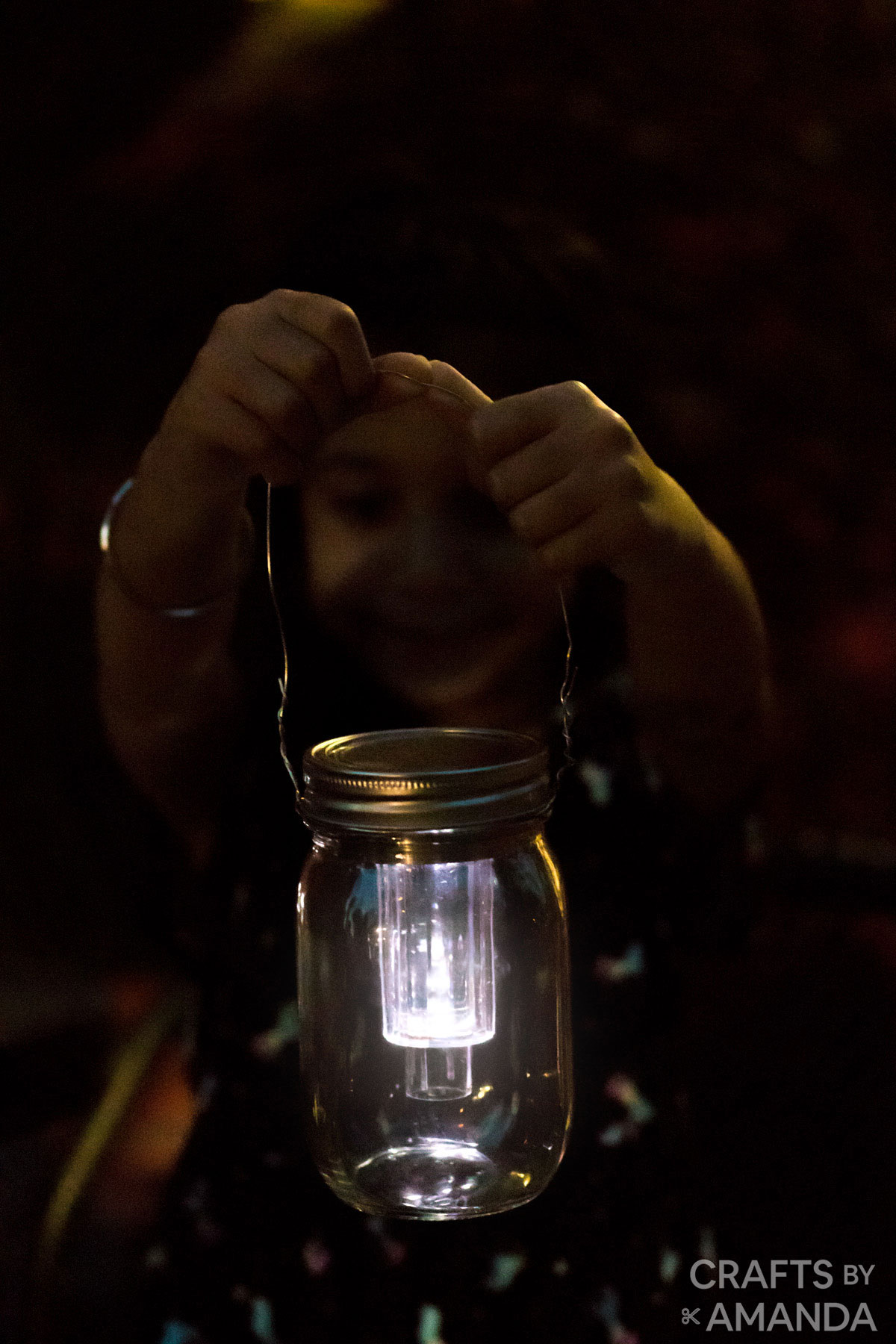 little girl holding mason jar solar light