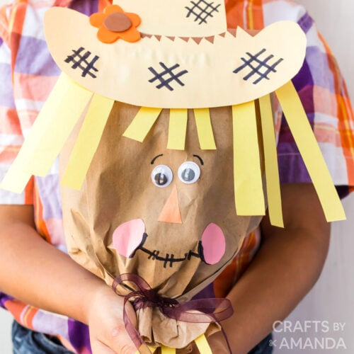 boy holding paper bag scarecrow