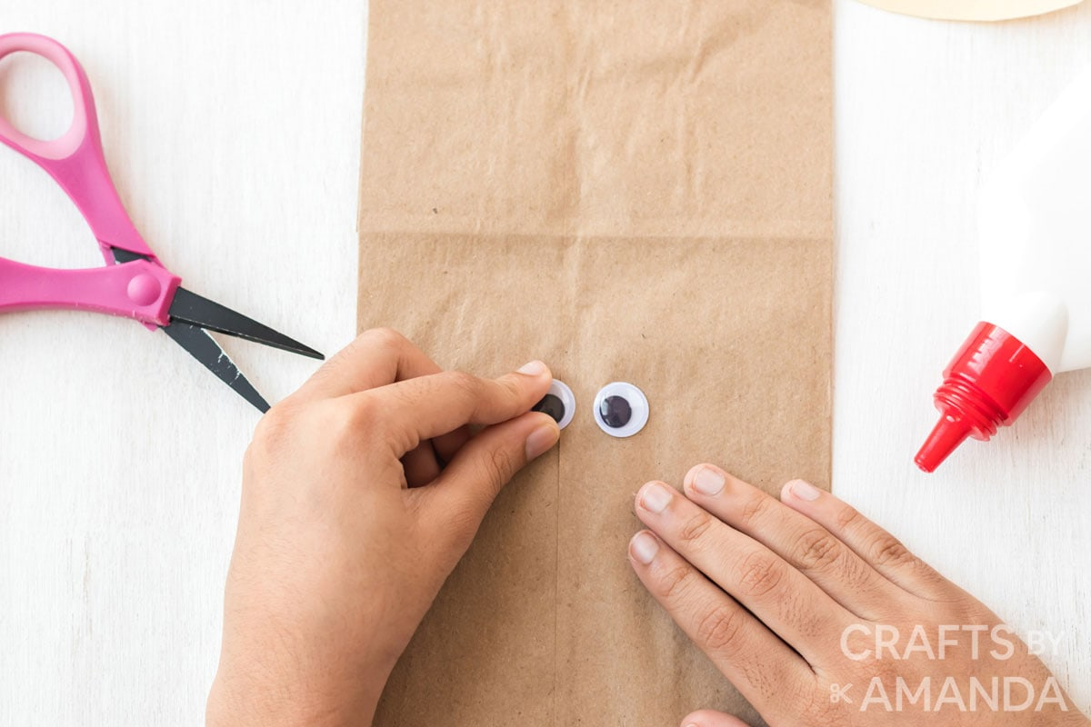 gluing googly eyes to paper bag