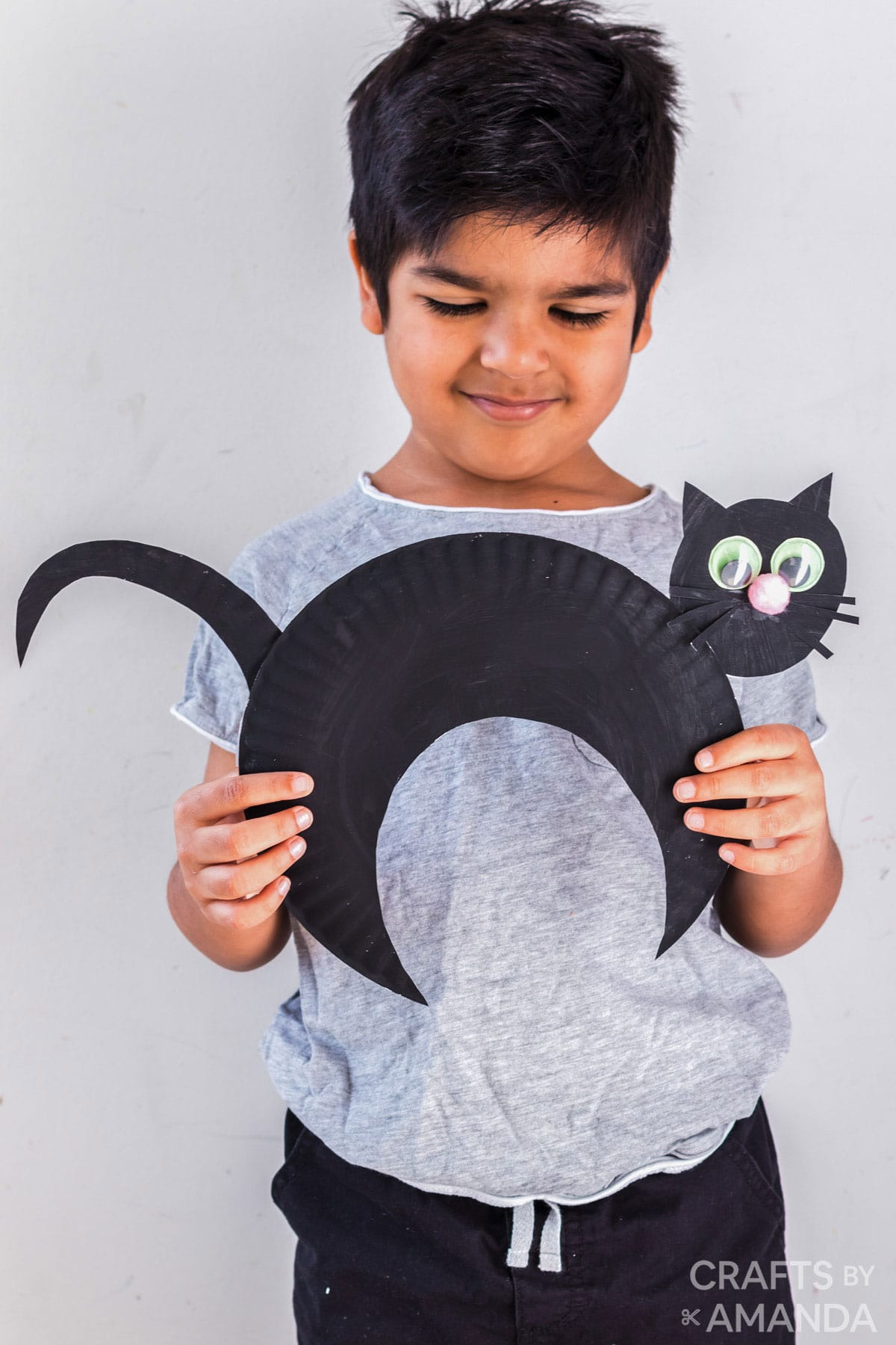 little boy holding black cat made from paper plate