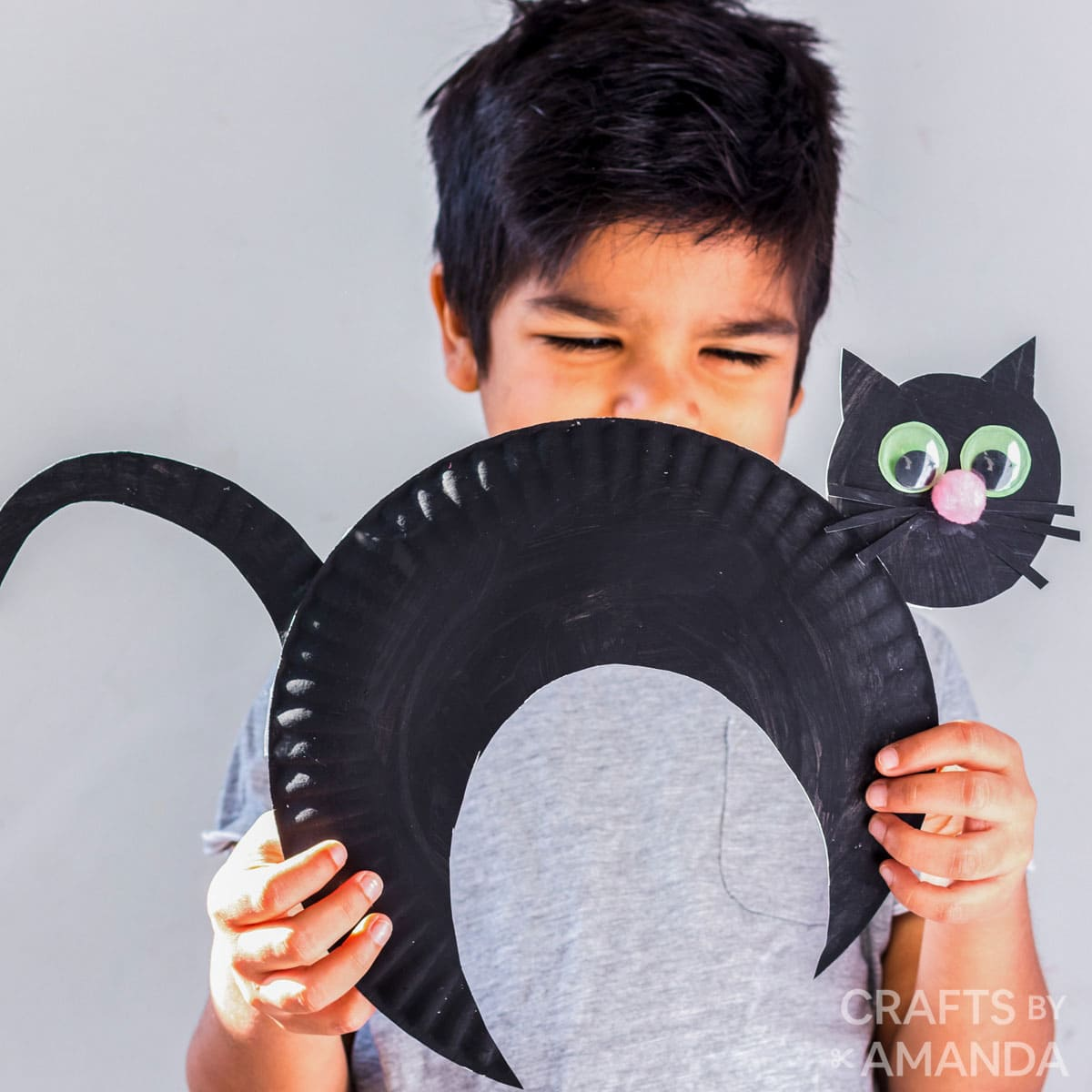 little boy smiling behind paper plate black cat craft