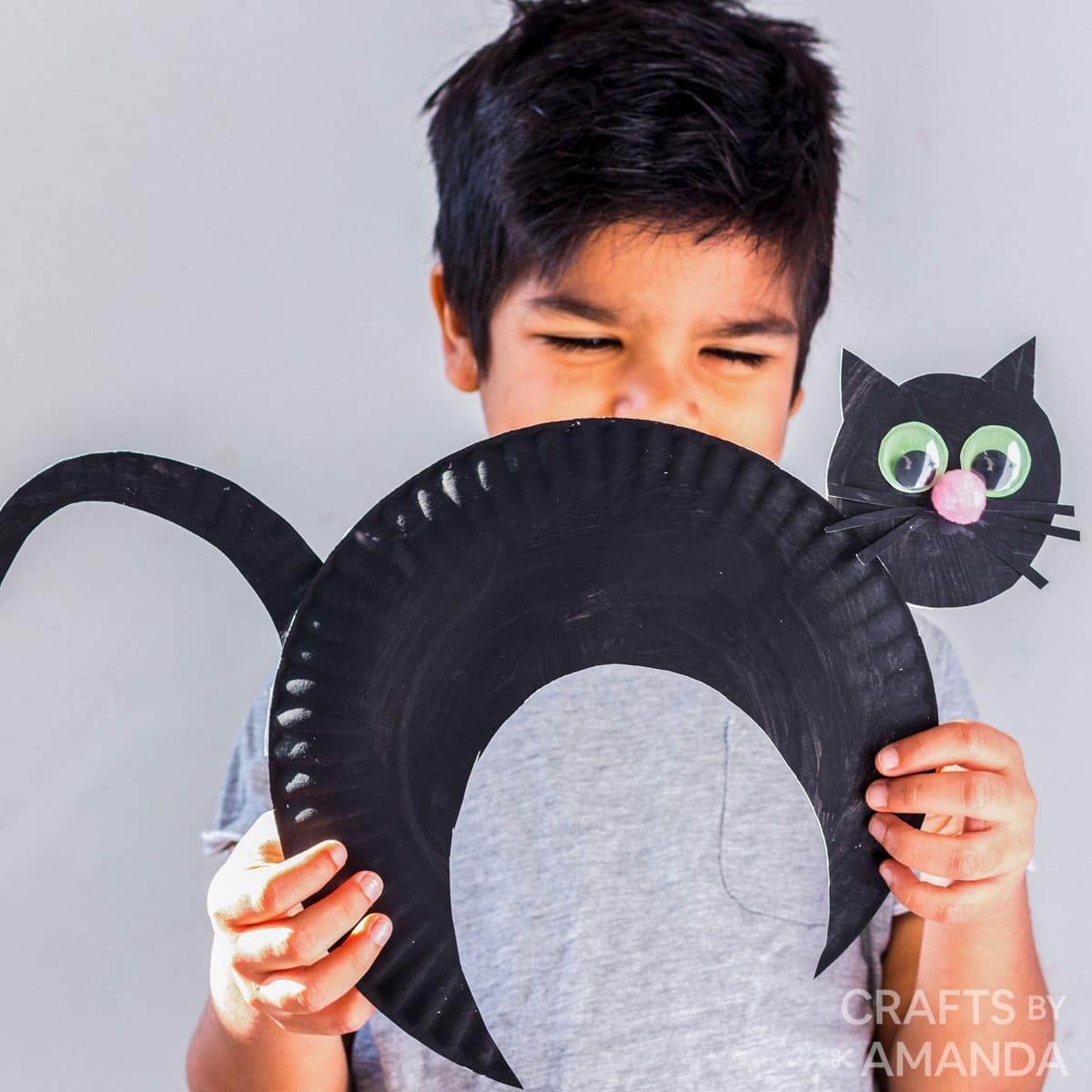 little boy smiling behind paper plate black cat craft