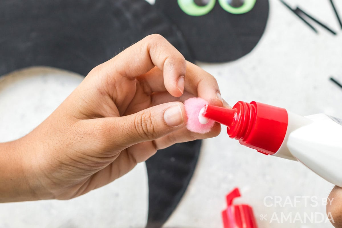 adding glue to a pom pom