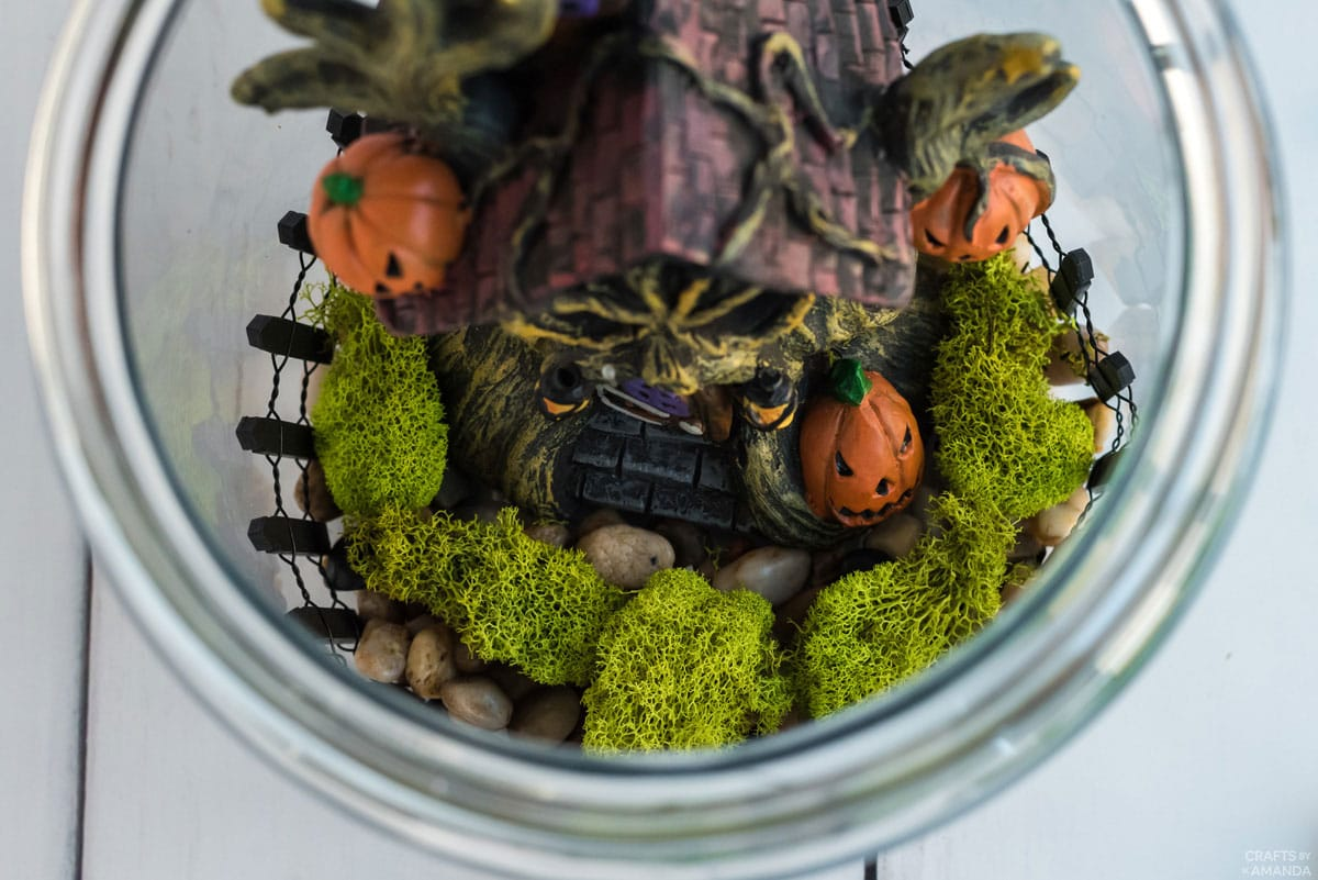 haunted house figurine with moss inside glass canister