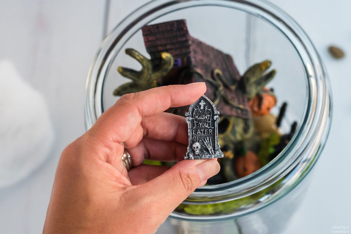 hand holding tiny gravestone figurine