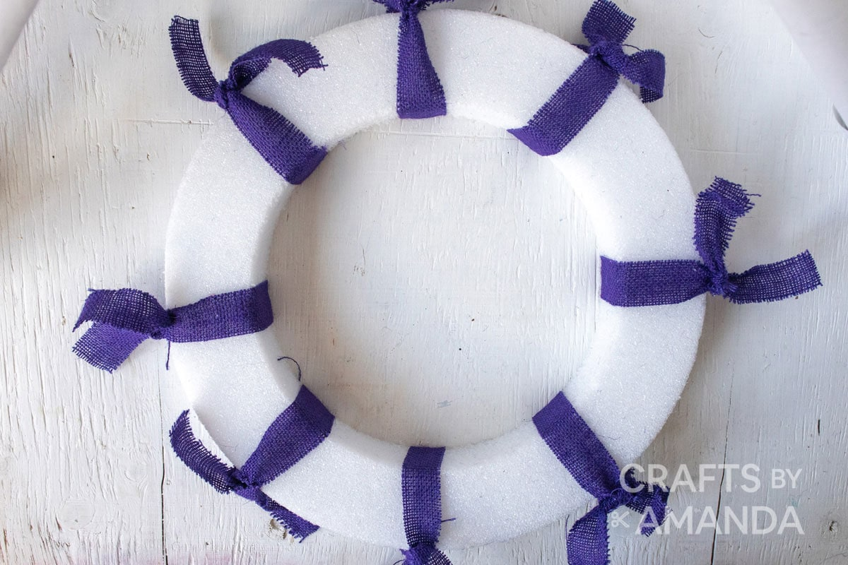 wreath form with purple ribbon wrapped around it