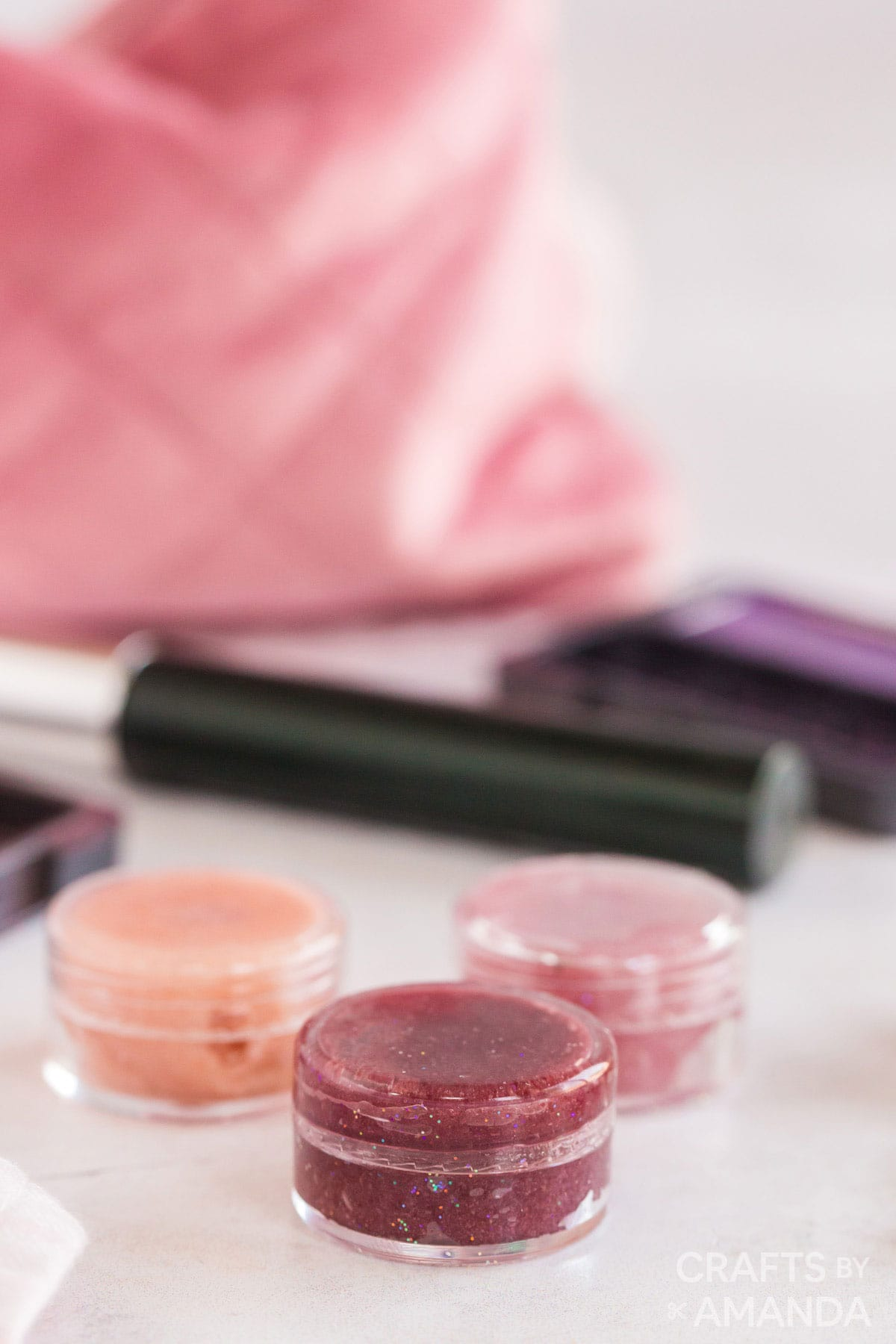 lip gloss with makeup supplies in background