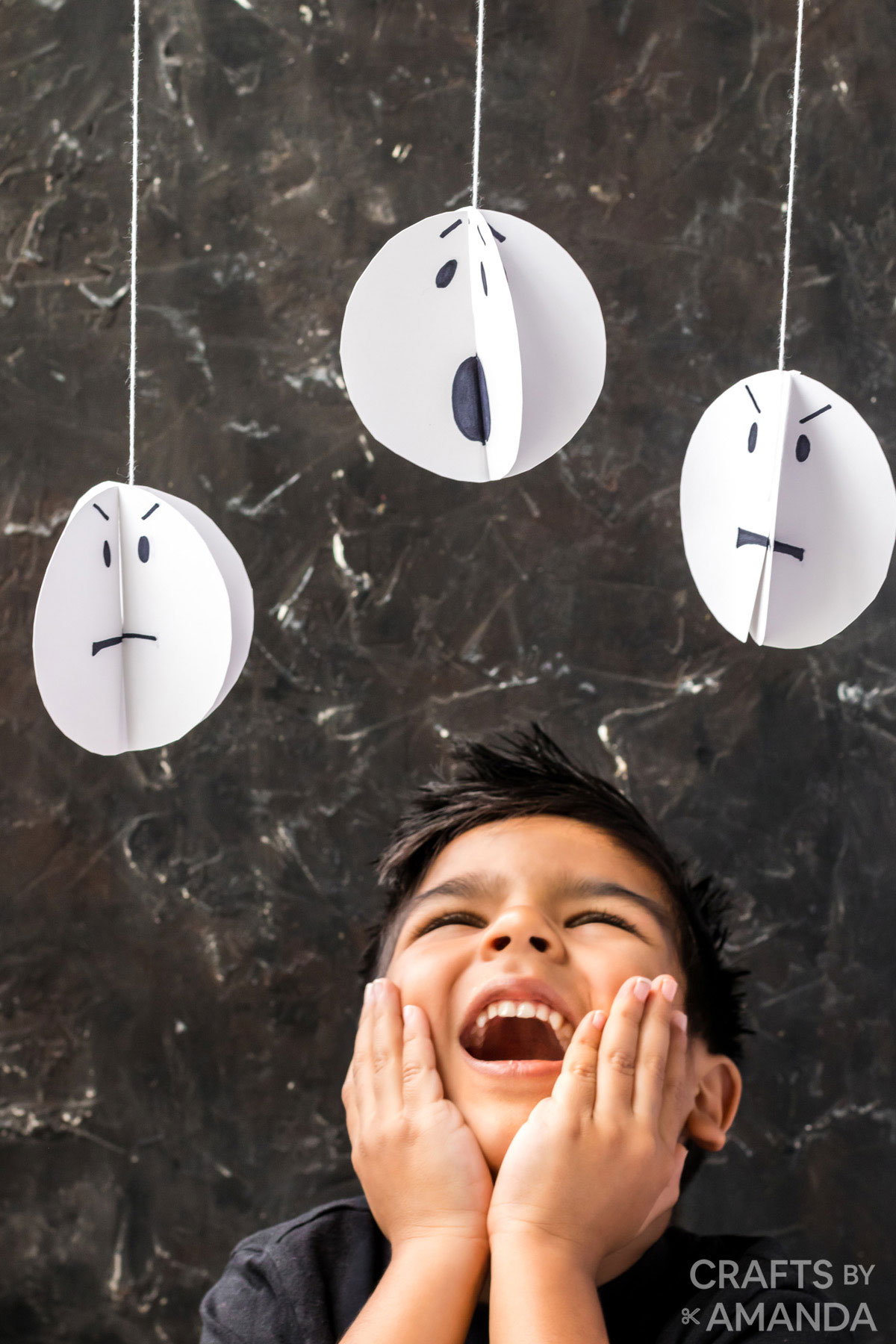 little boy with hands on cheeks looking up at paper ghosts