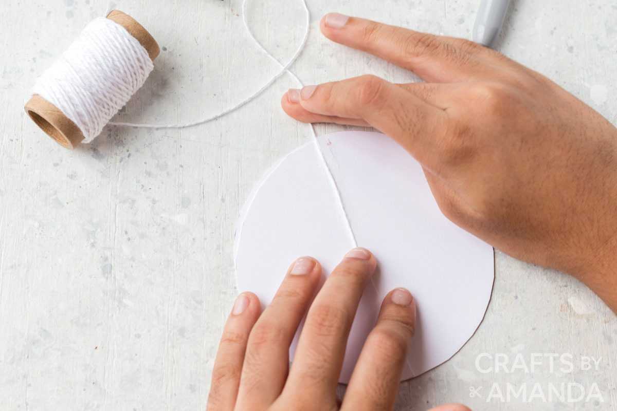 adding string to white paper circle