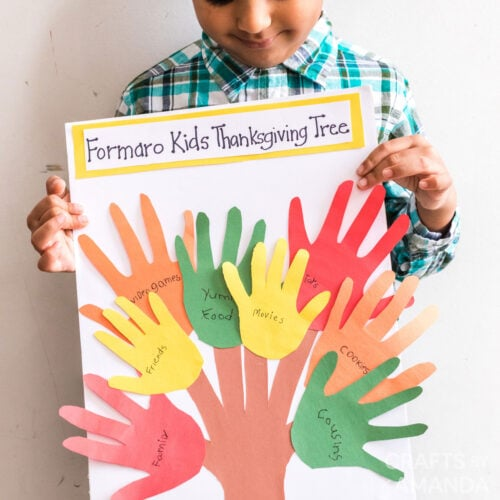 child holding thanksgiving handprint craft