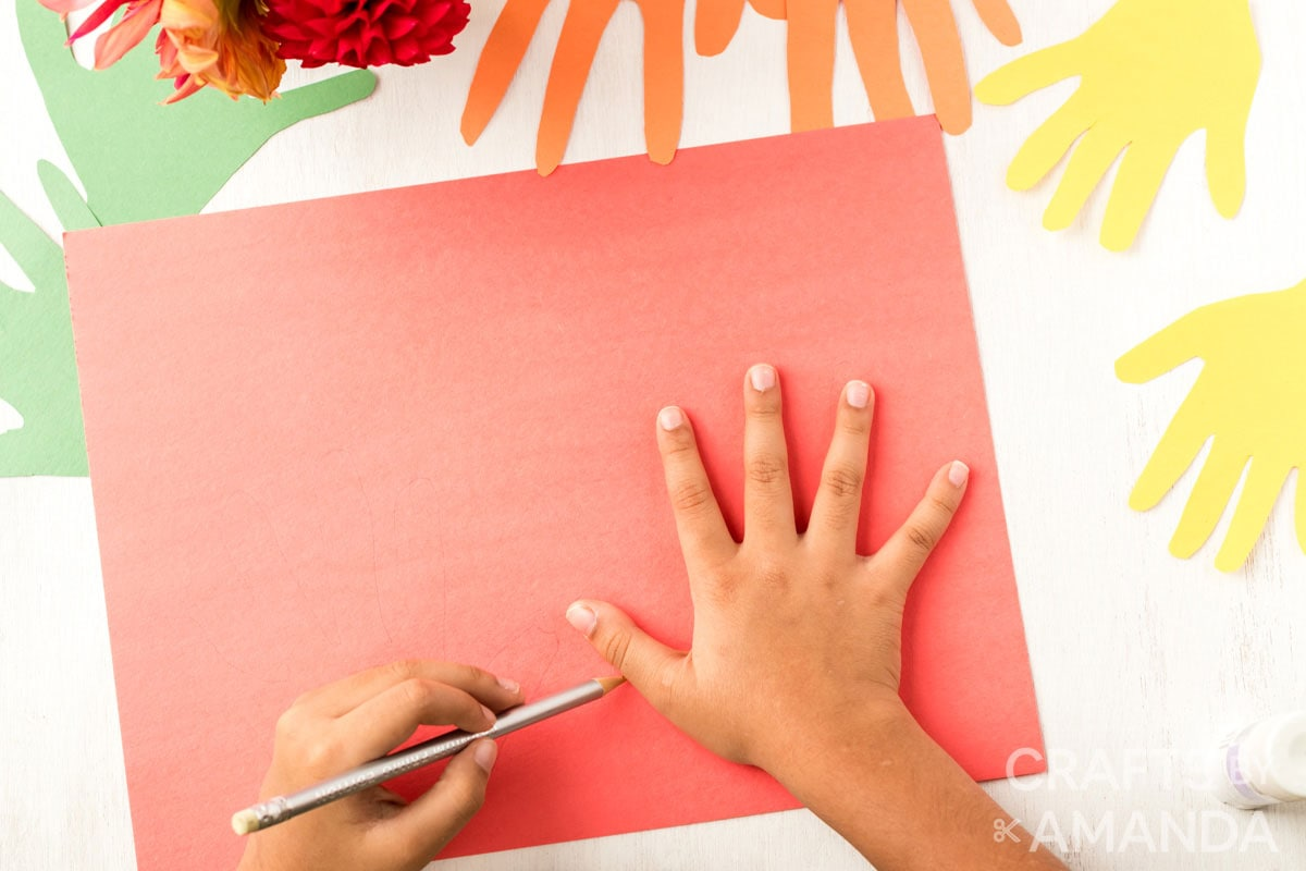 child tracing his hand on red paper