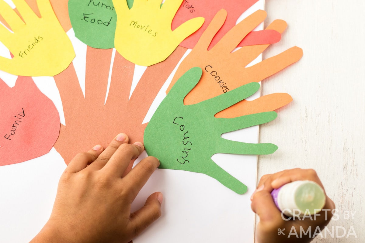 child glueing paper handprints to white board