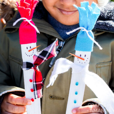 young boy holding paint stick snowmen