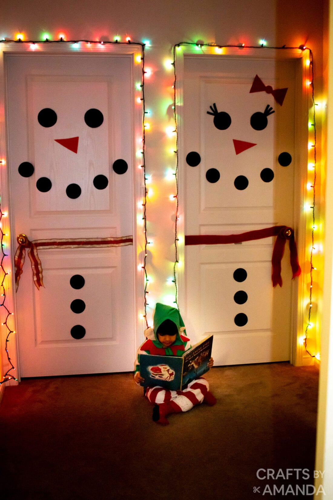 child reading book with snowman decorated doors in background