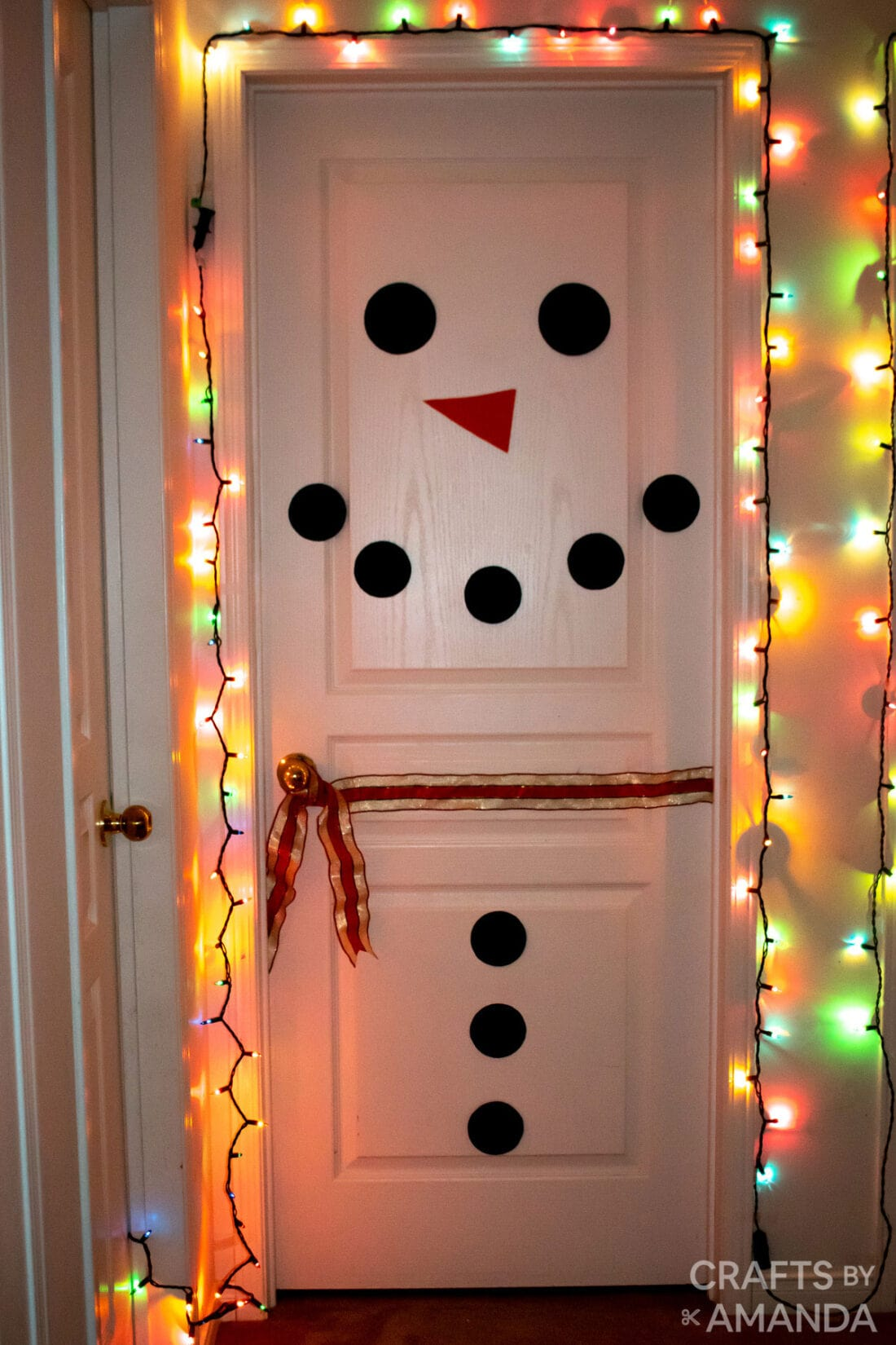 snowman decorated door with christmas lights around it