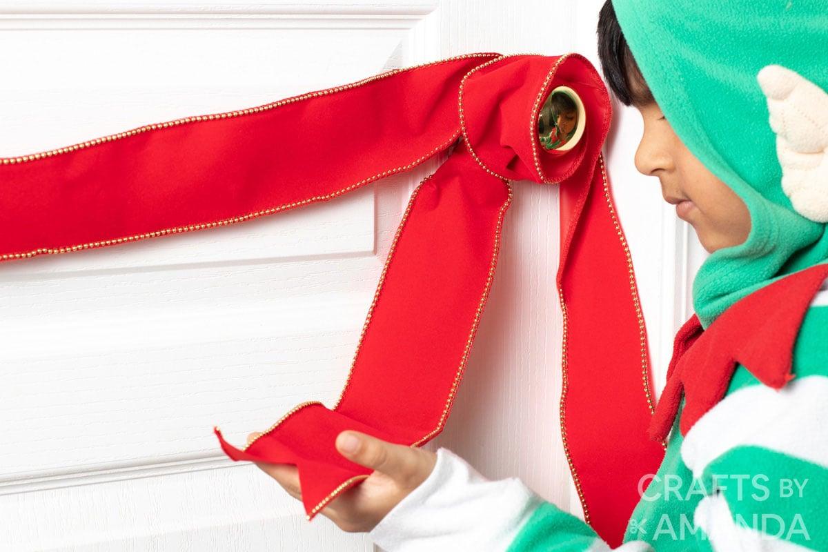 child wrapping ribbon around door knob