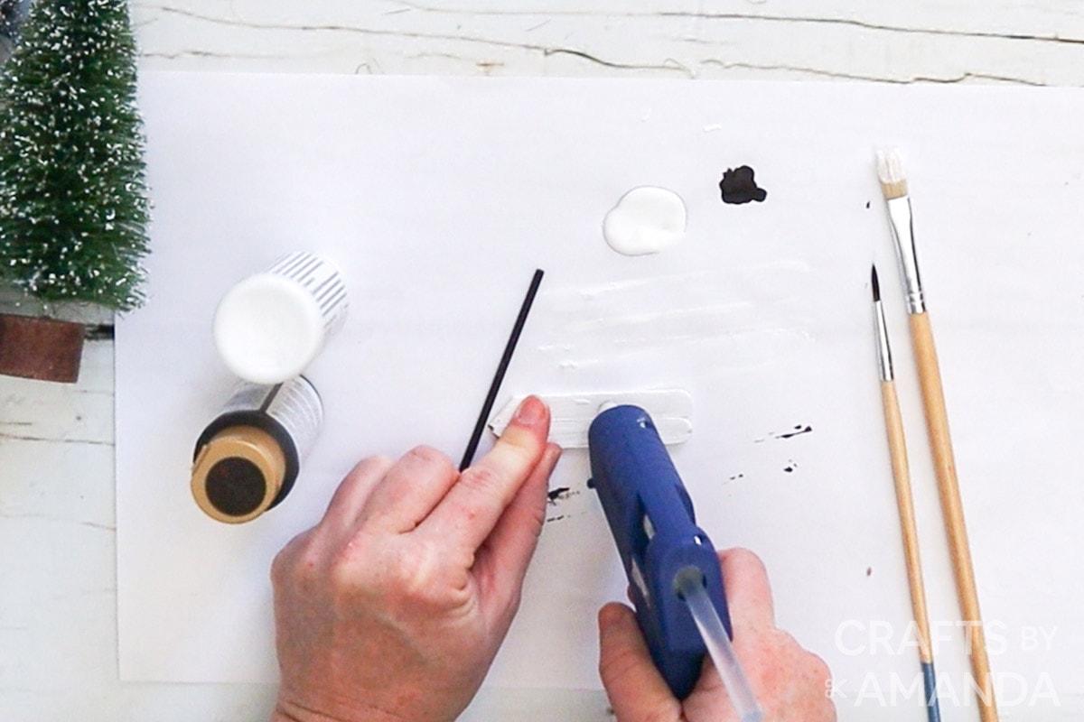 adding hot glue to sticks