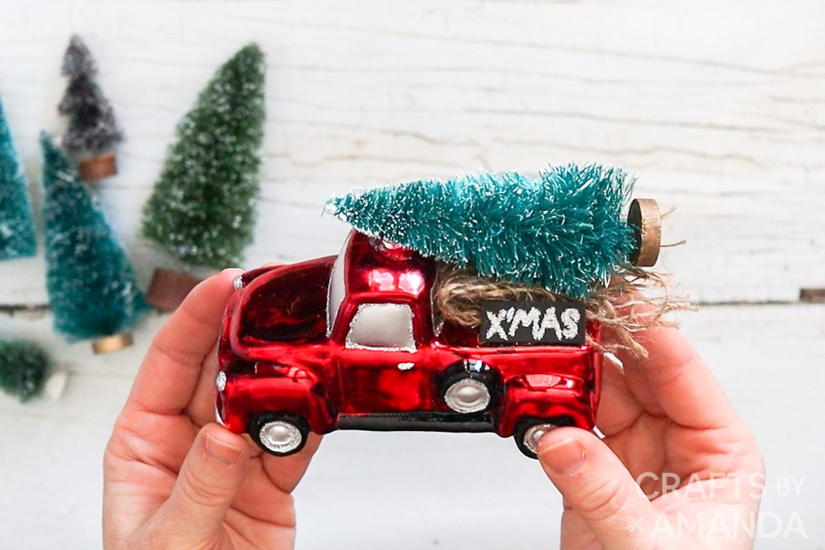 holding red truck ornament