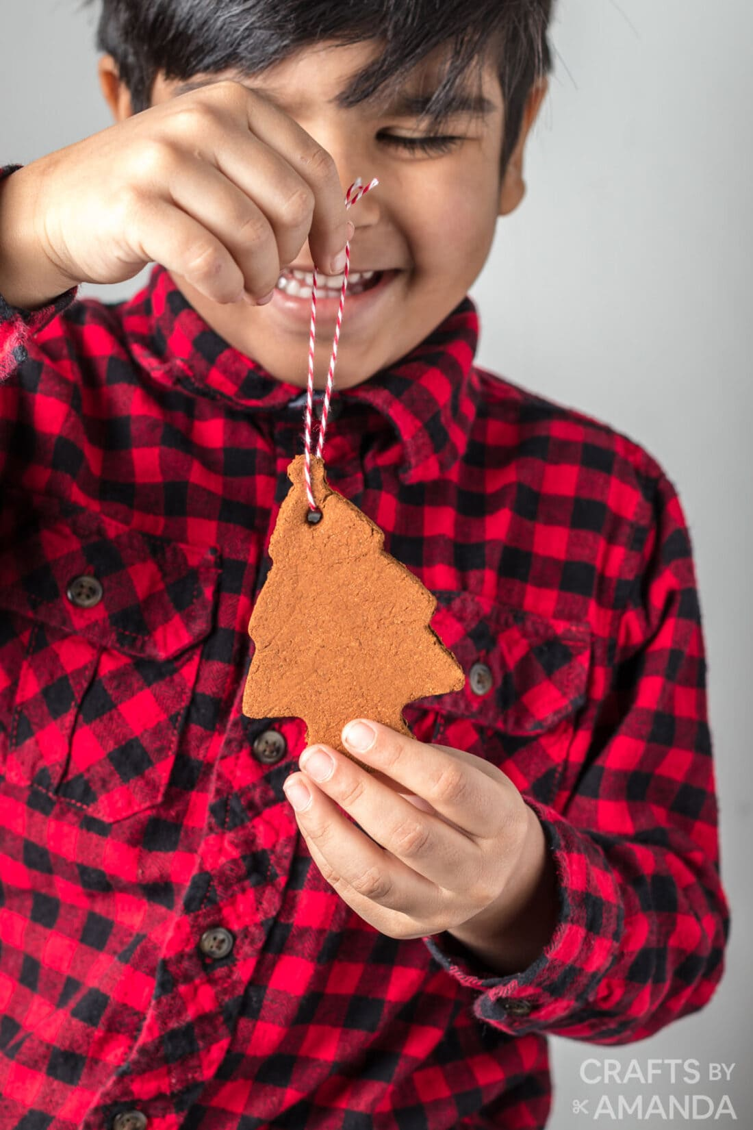 boy holding cinnamon ornament