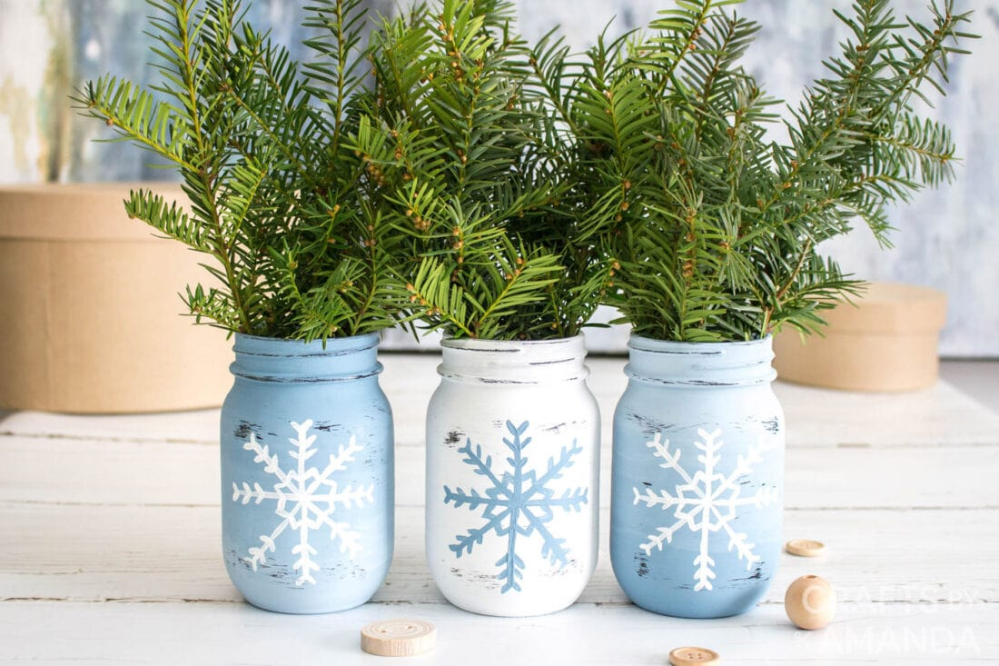 3 painted jars with pine sprigs