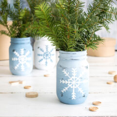 3 snowflake mason jars with sprigs on pine