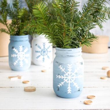 3 snowflake mason jars with sprigs on pine