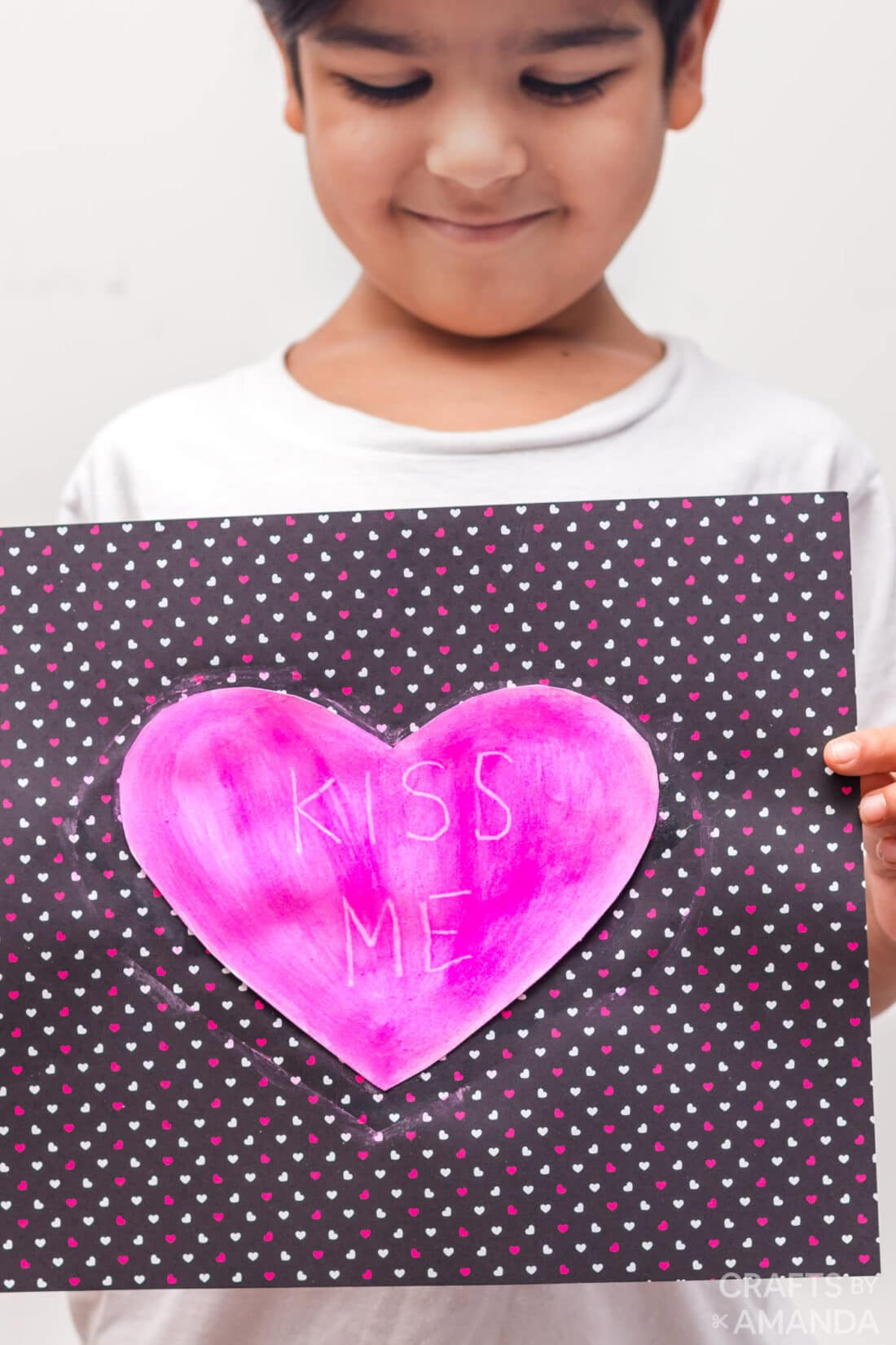chil holding heart shaped painting