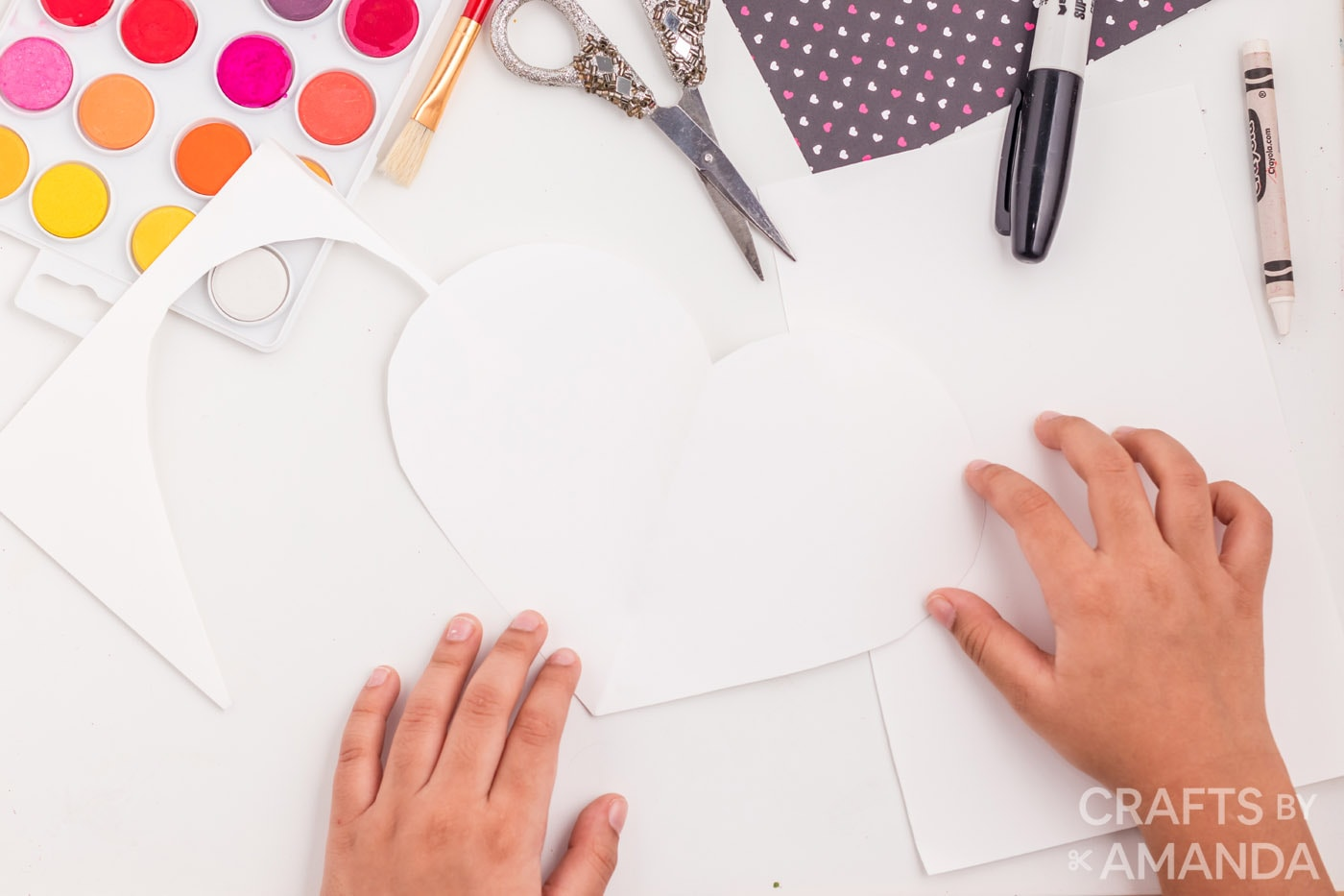 cutting out a heart from the small pieces of paper