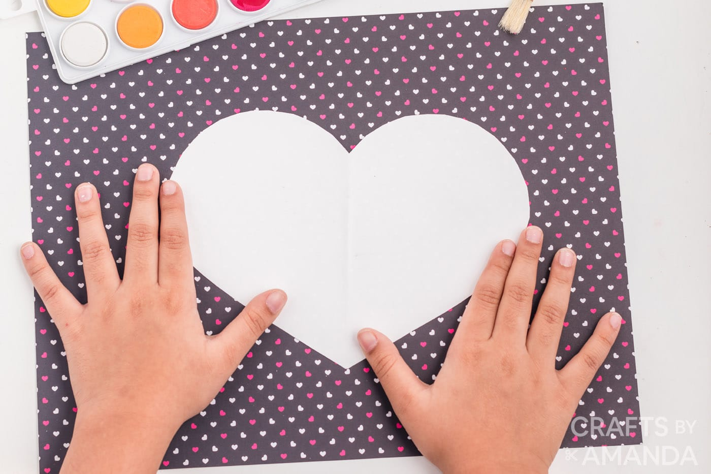 adhering white heart to construction paper