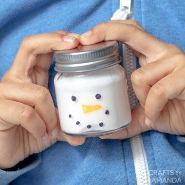 boy holding jar of snowman slime