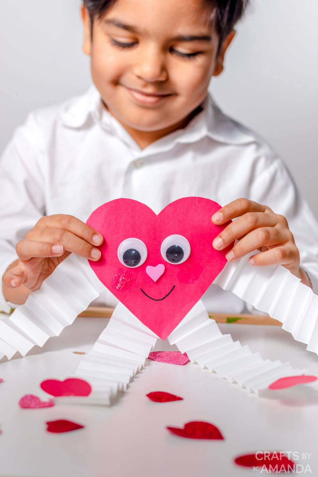 child holding paper valentine heart man with accordion arms