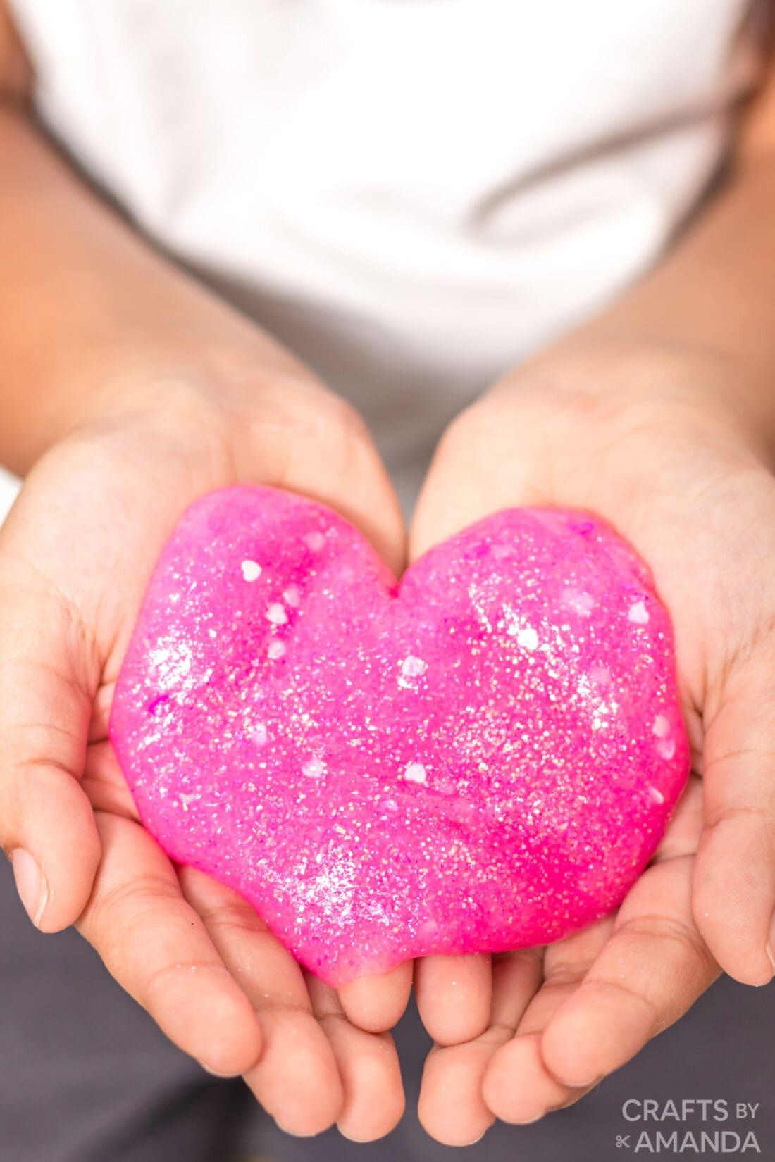 child holding pink valentine slime