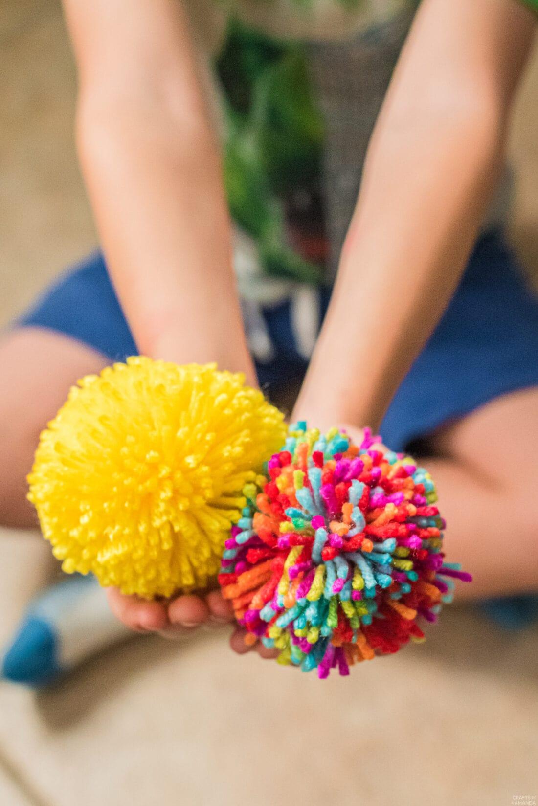 child holding two homemade yarn pom poms
