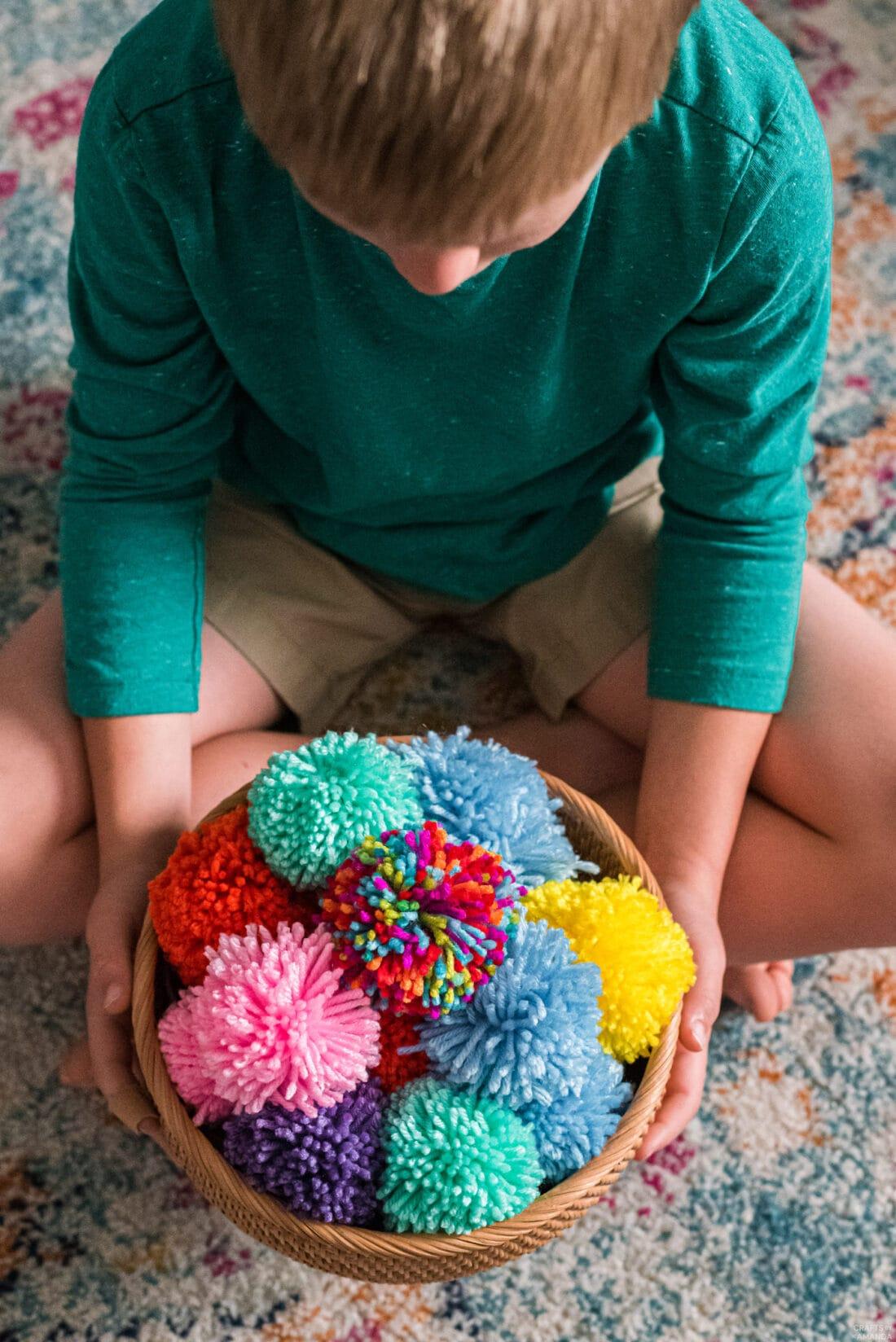 child holding a basket full of DIY yarn pom poms