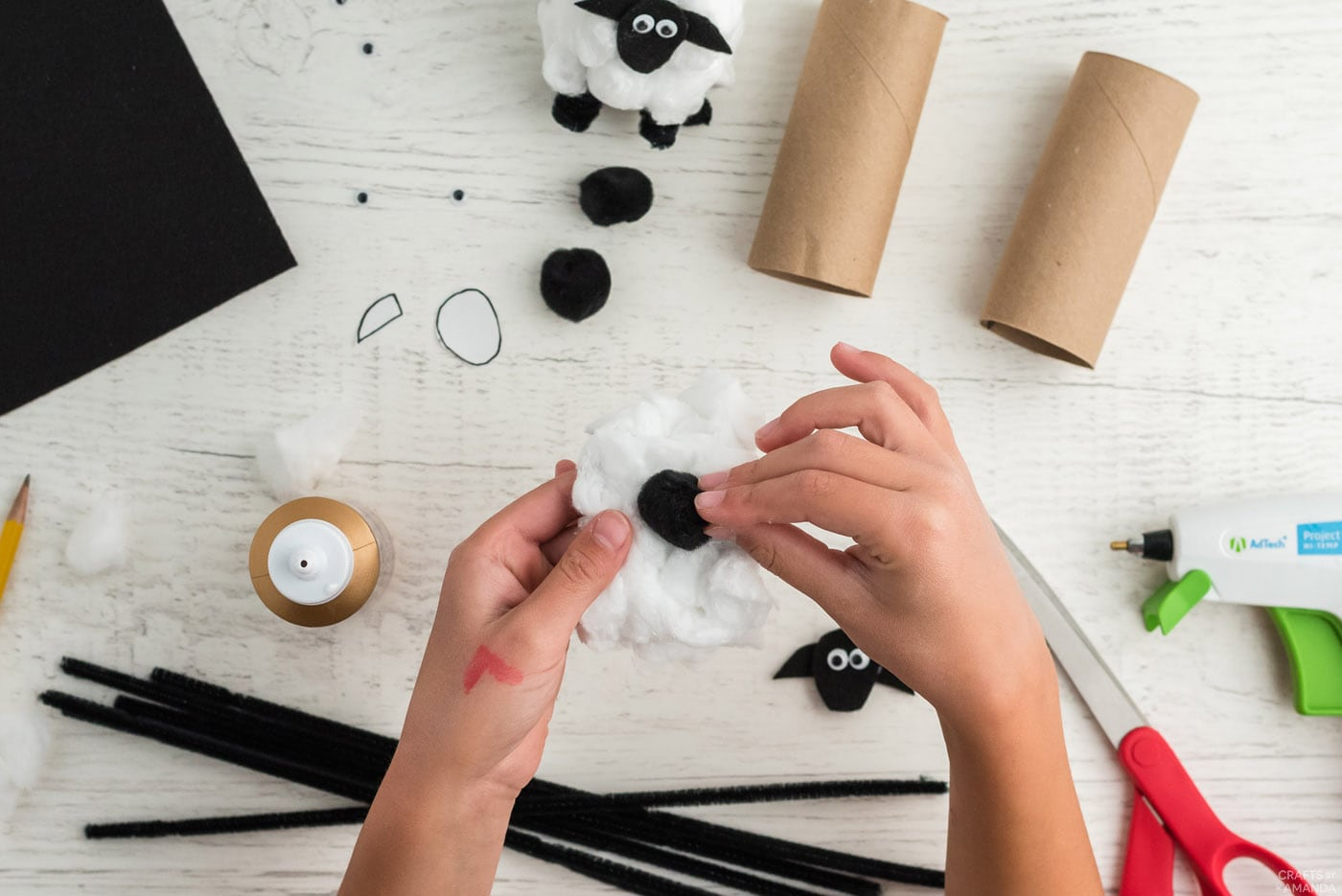gluing a black pom pom onto cotton ball covered cardboard tube