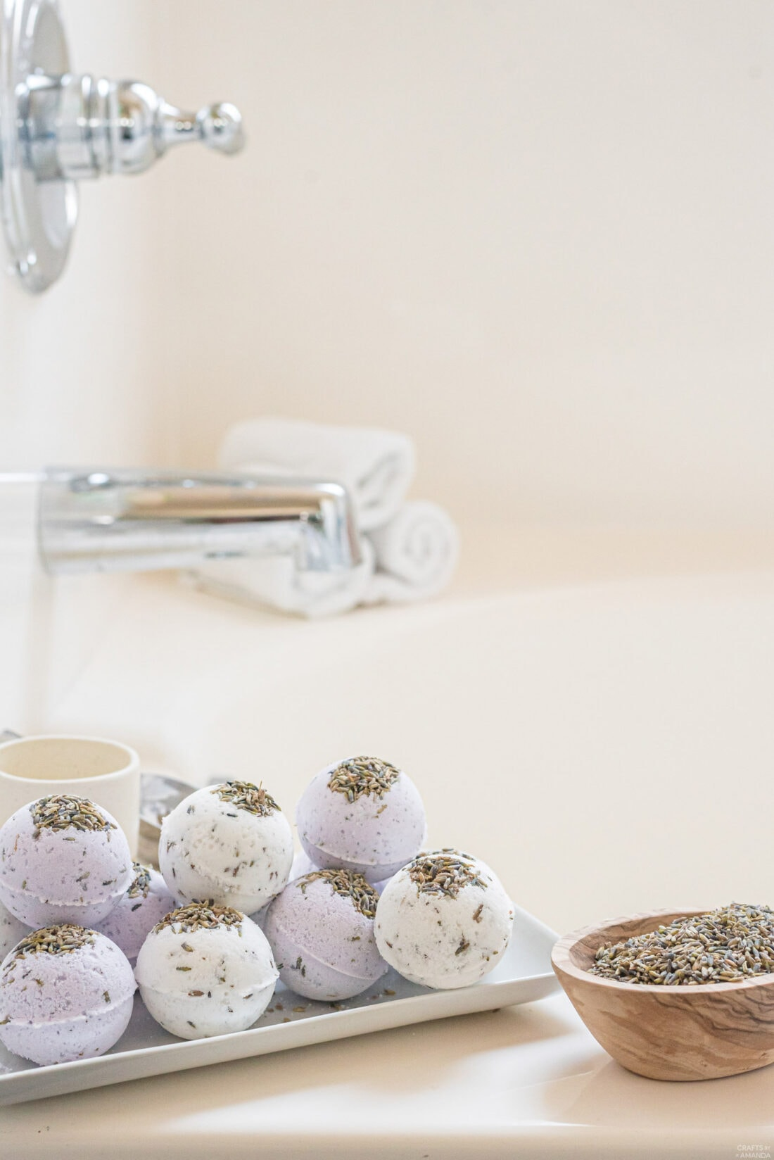 lavender bath bombs on tray by bathtub