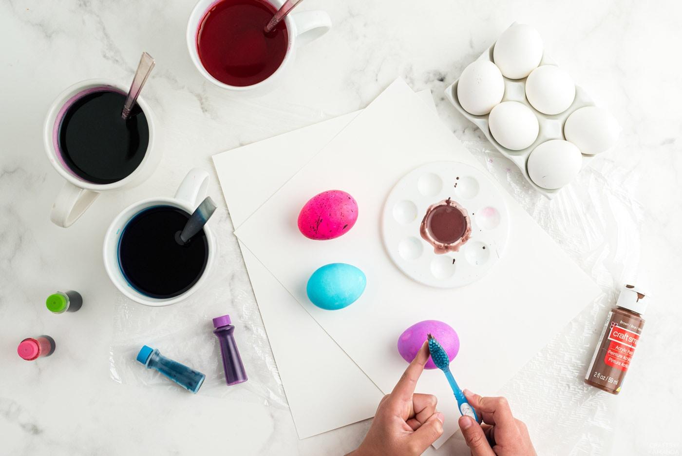 utiliser une brosse à dents pour appliquer de la peinture sur des œufs colorés