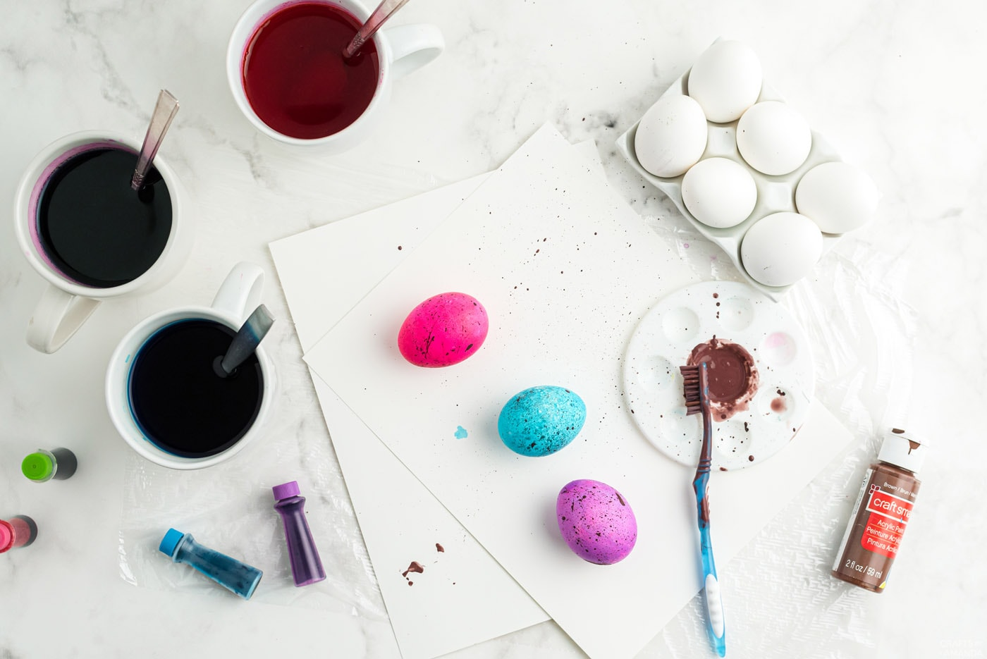 using a toothbrush to flick paint onto colored eggs