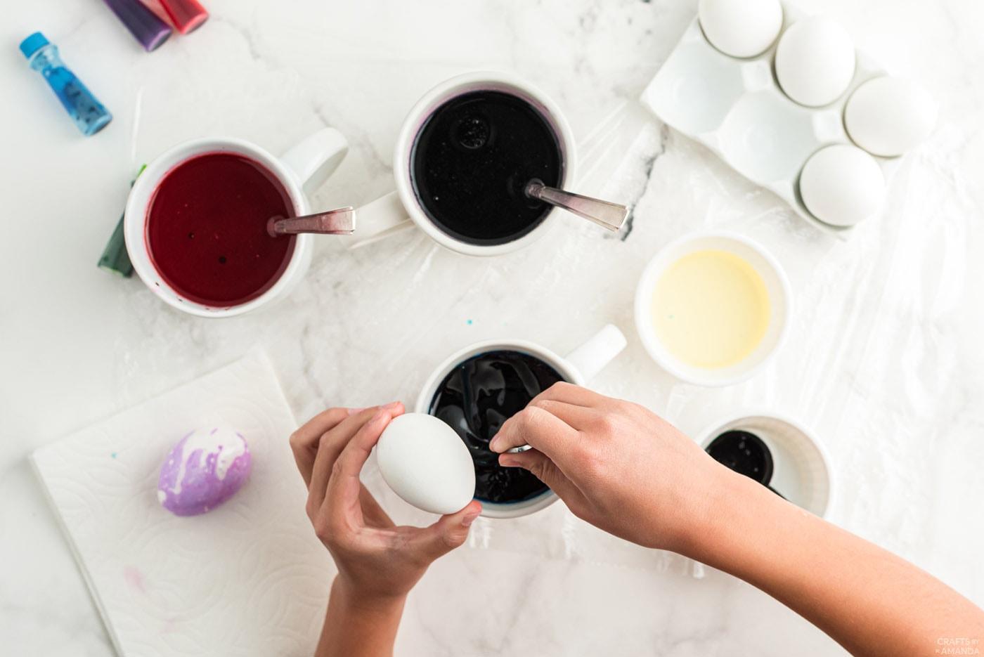 vinaigre tourbillonnant, colorant alimentaire et eau dans une tasse avec une cuillère