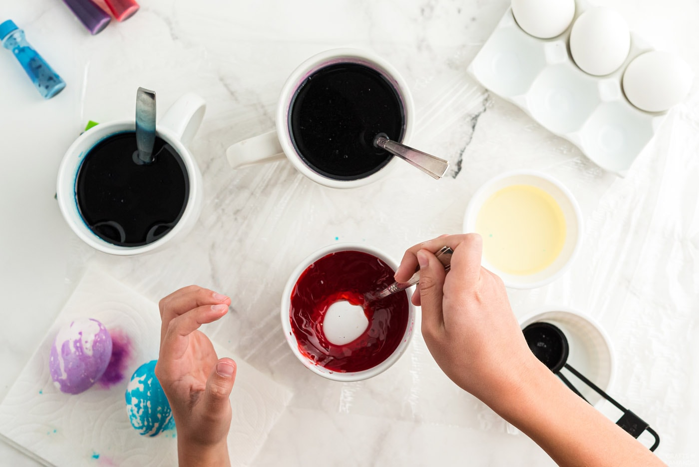 Placer l'œuf sur une cuillère dans l'eau et le mélange de colorant alimentaire
