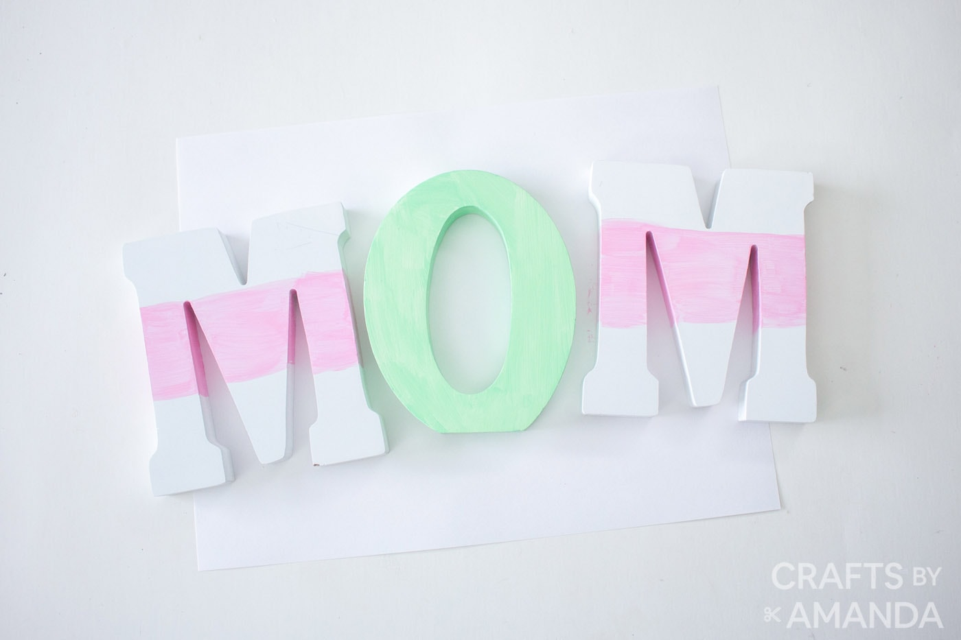 Mom spelt out in wood letters with O being green