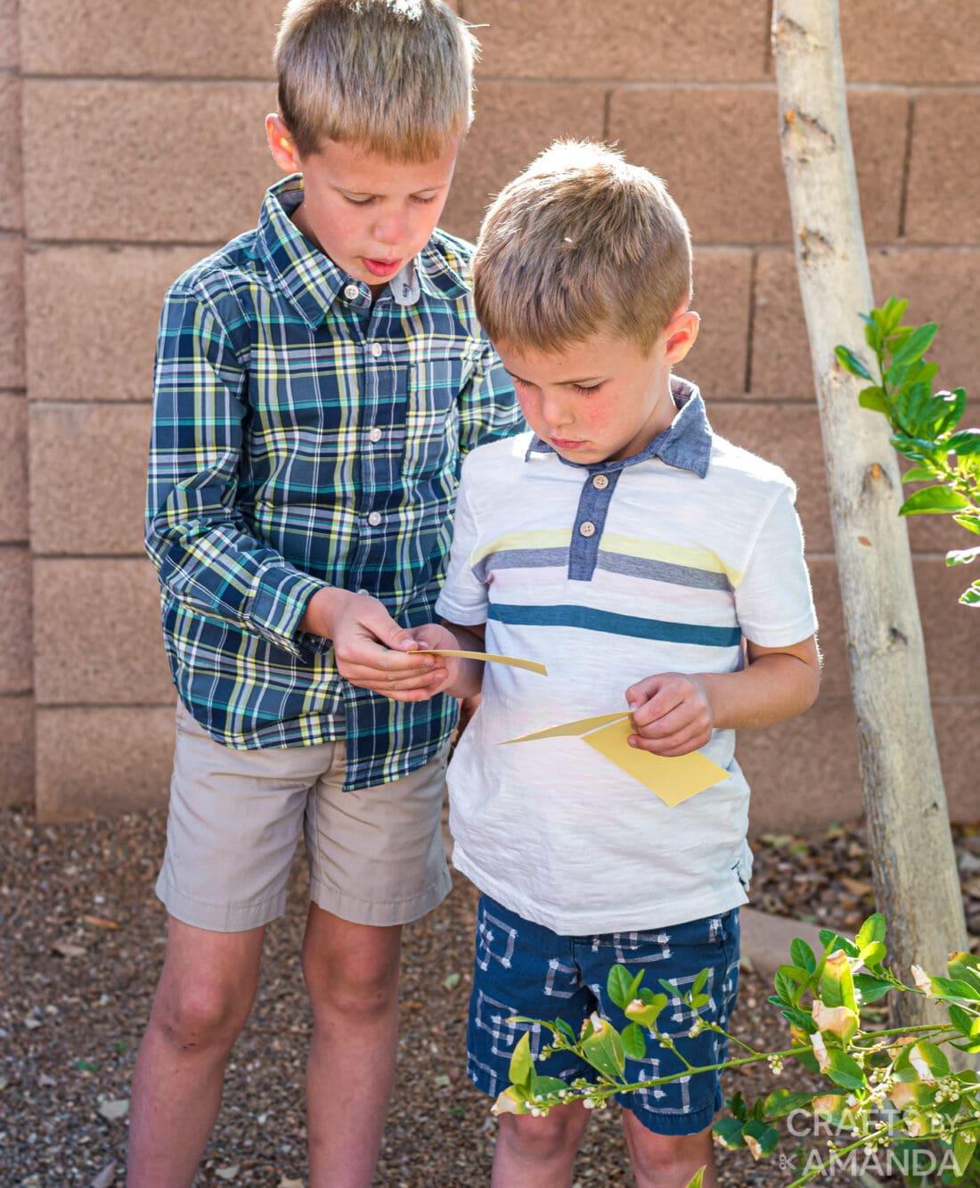 enfants tenant des cartes de chasse au trésor de pâques