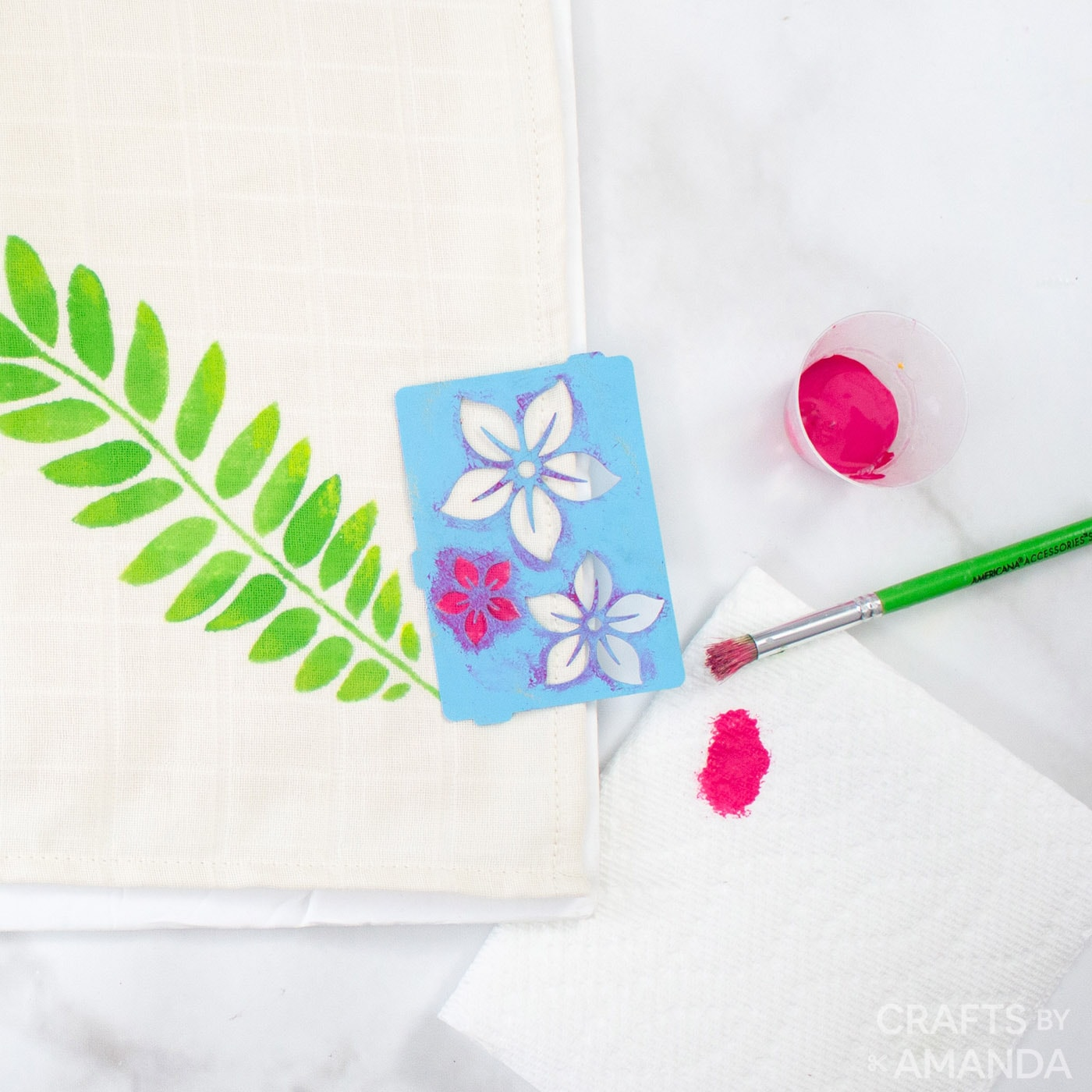 stenciling bright pink flowers onto towel