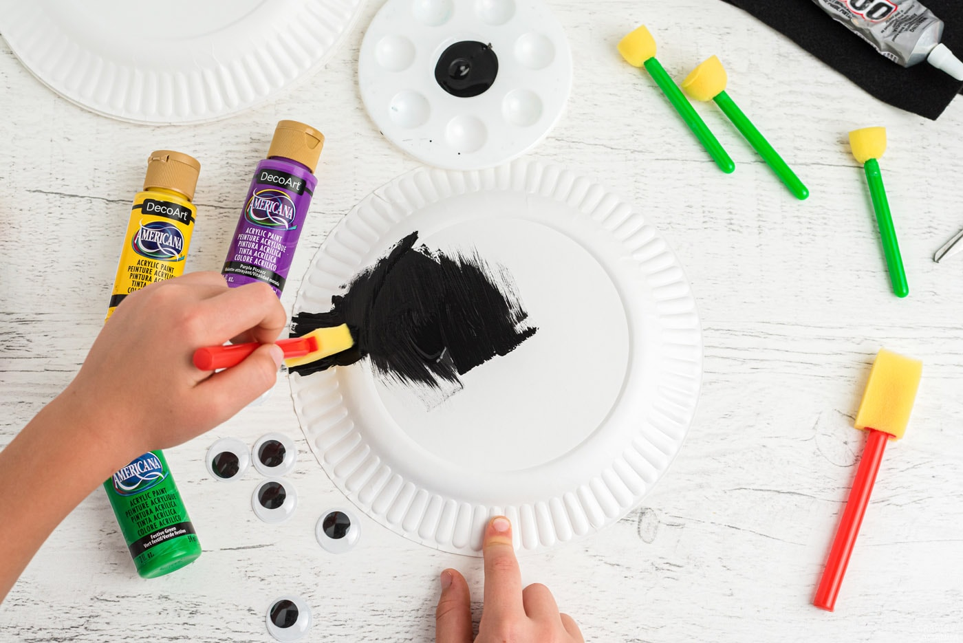 child painting paper plate black