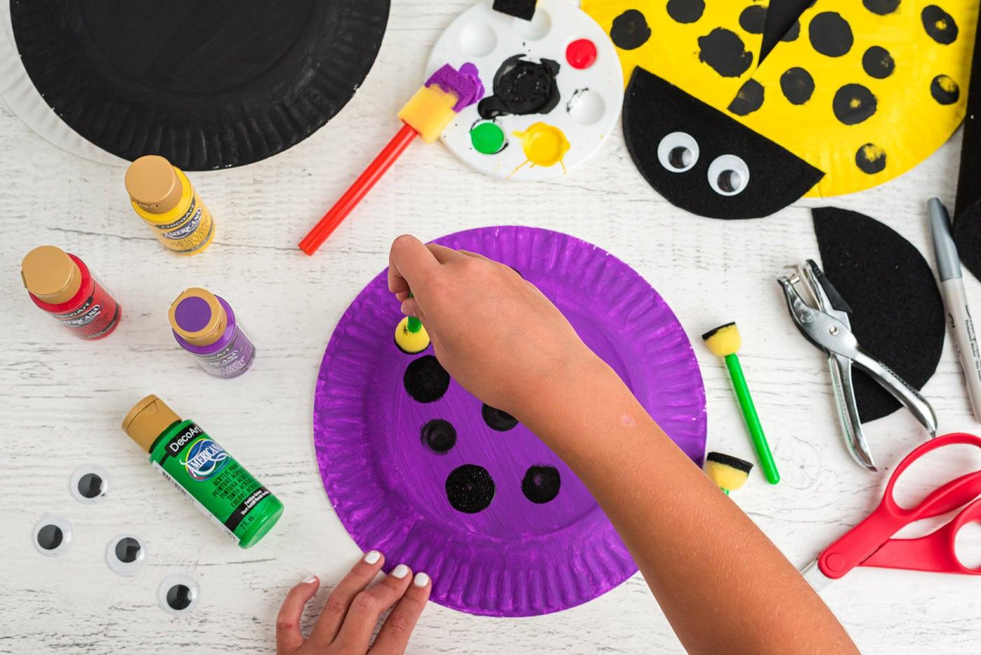 kids hand using a pouncer sponge to make black polka dots onto paper plate