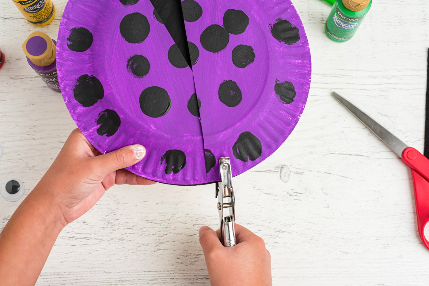 using a hole punch in a paper plate