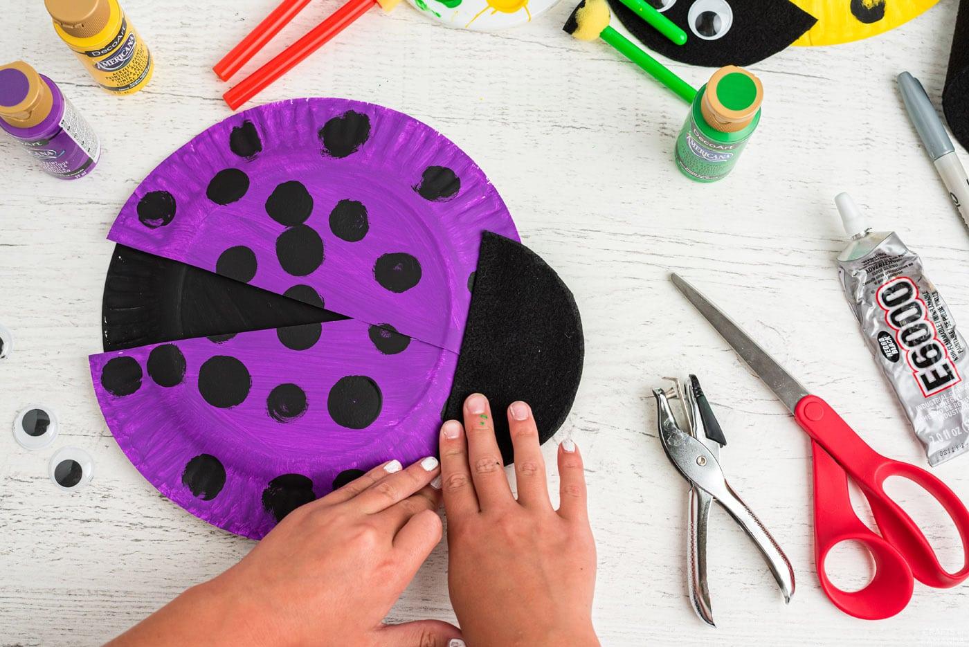 gluing felt head to ladybug paper plate