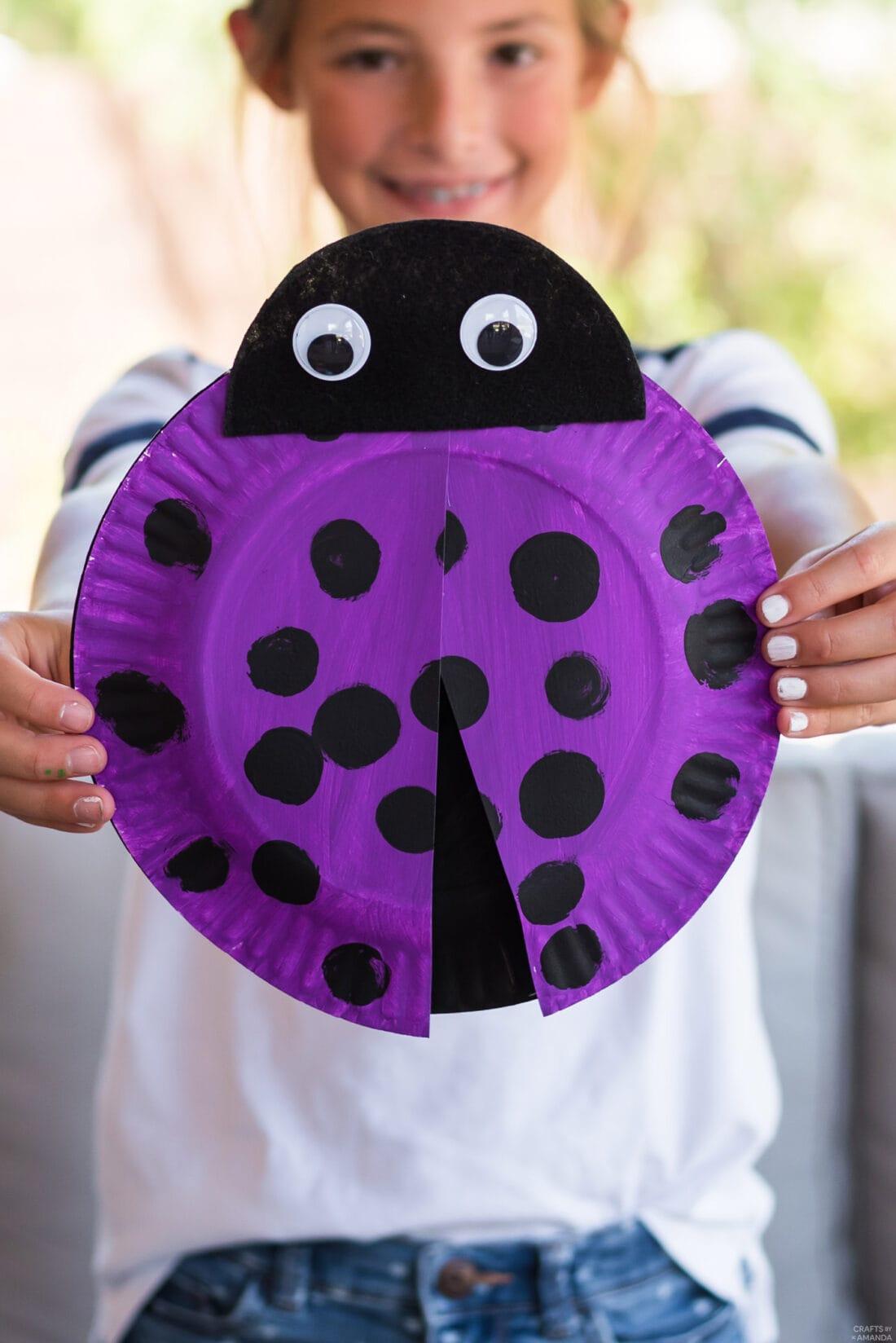 girl holding paper plate ladybug she made