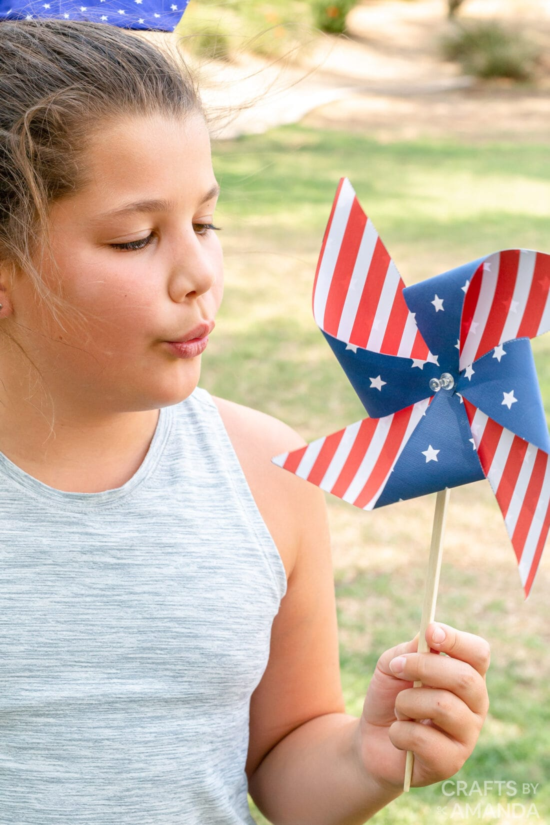 girl blowing on pinwheel